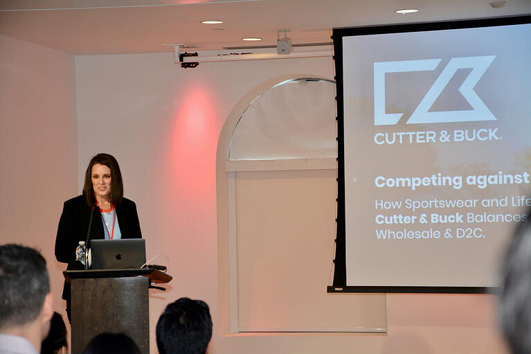 A woman with brown hair and a blue blazer speaks from behind a podium. A screen with the logo of Cutter & Buck is projected in the background.