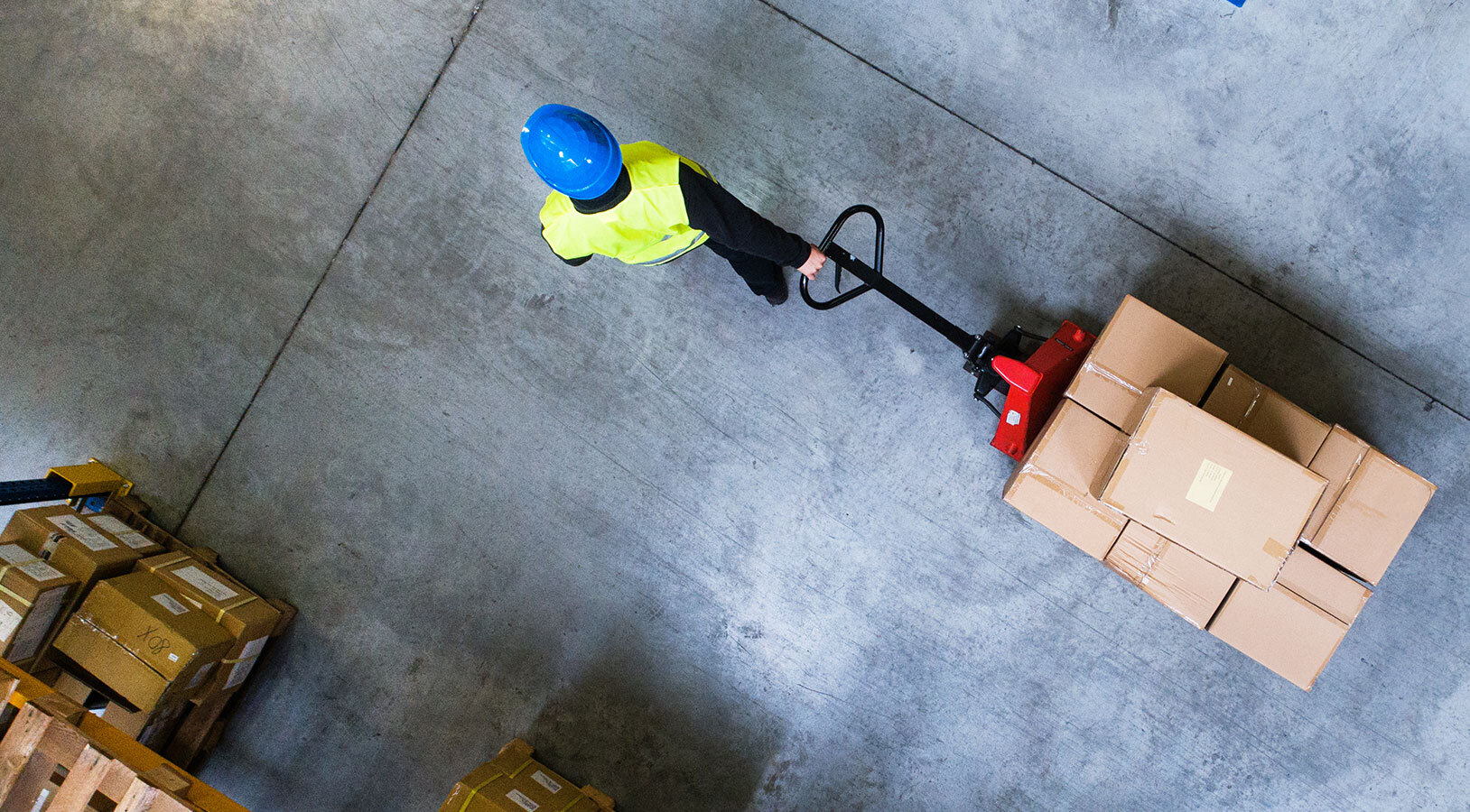 View from above of a person pulling boxes in a warehouse.
