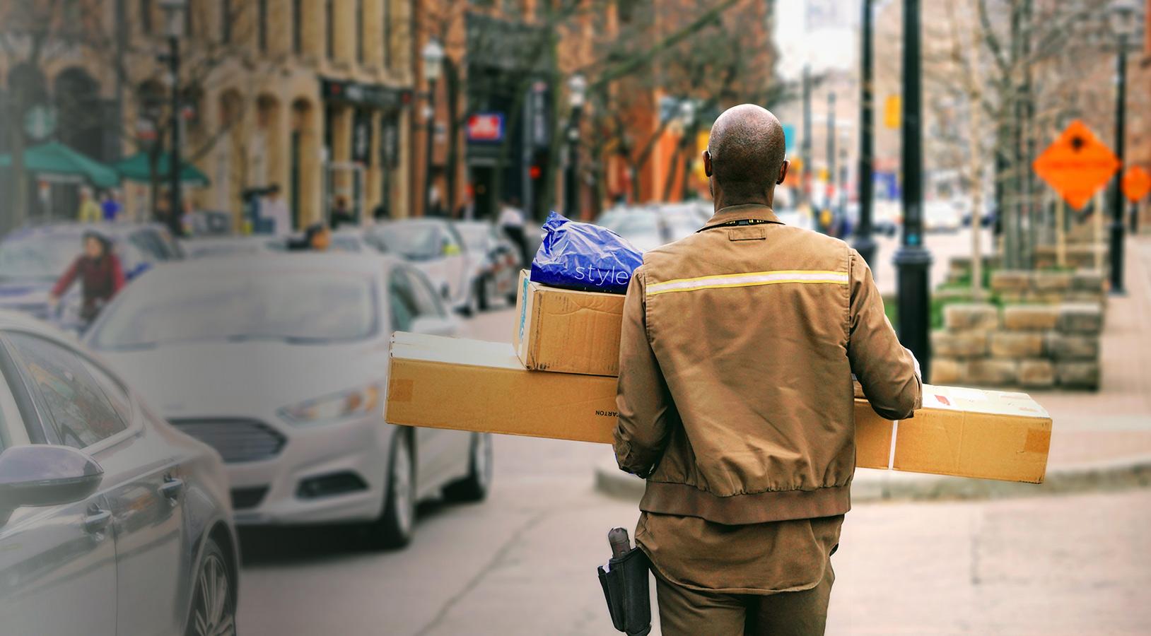 Livreur se promenant avec des colis lors d'une livraison
