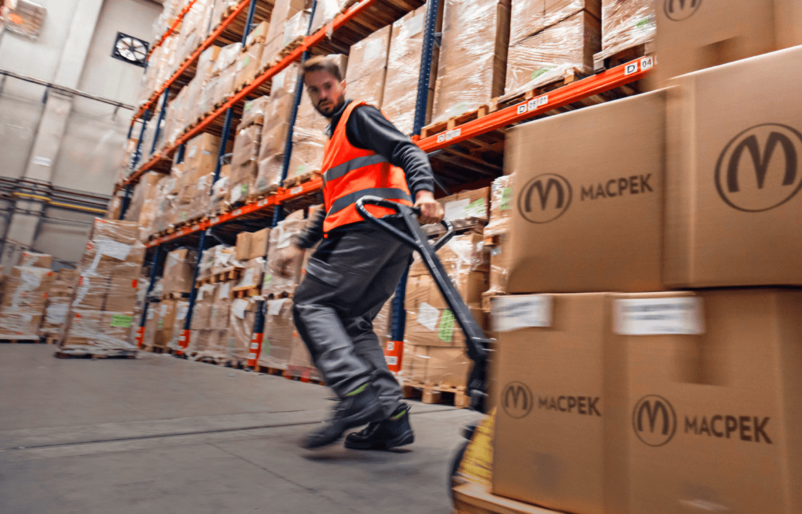 Worker pulling a cart in a MacPek warehouse