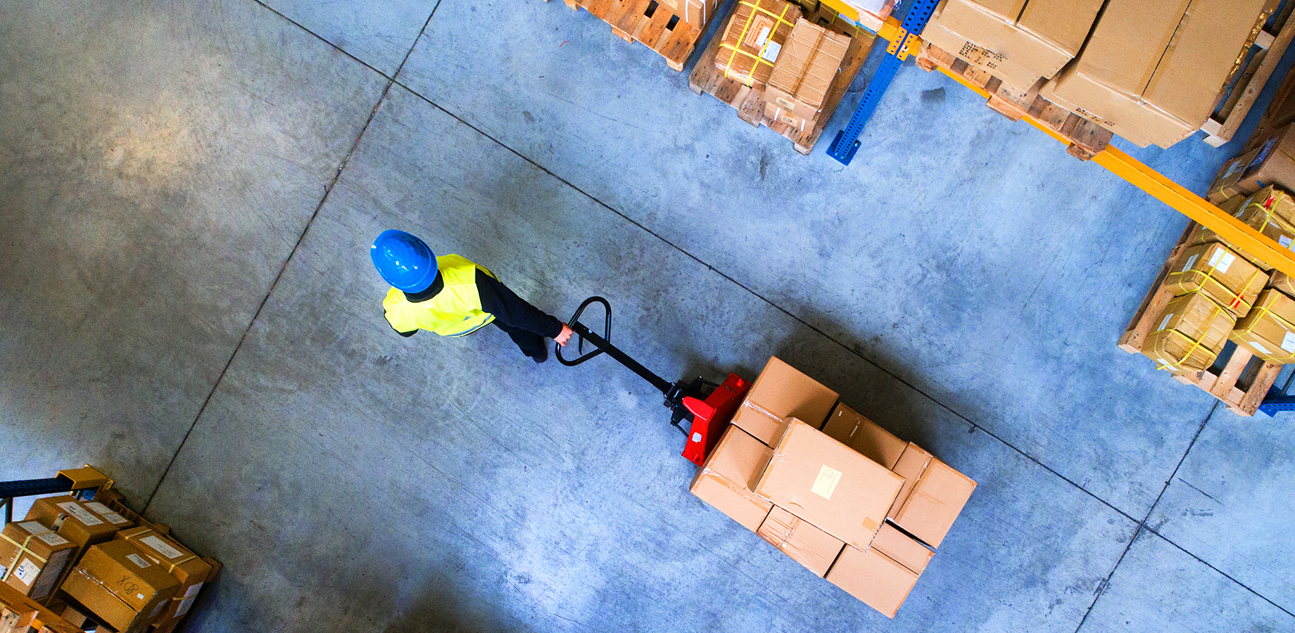 Man pulling a product cart in a distribution warehouse