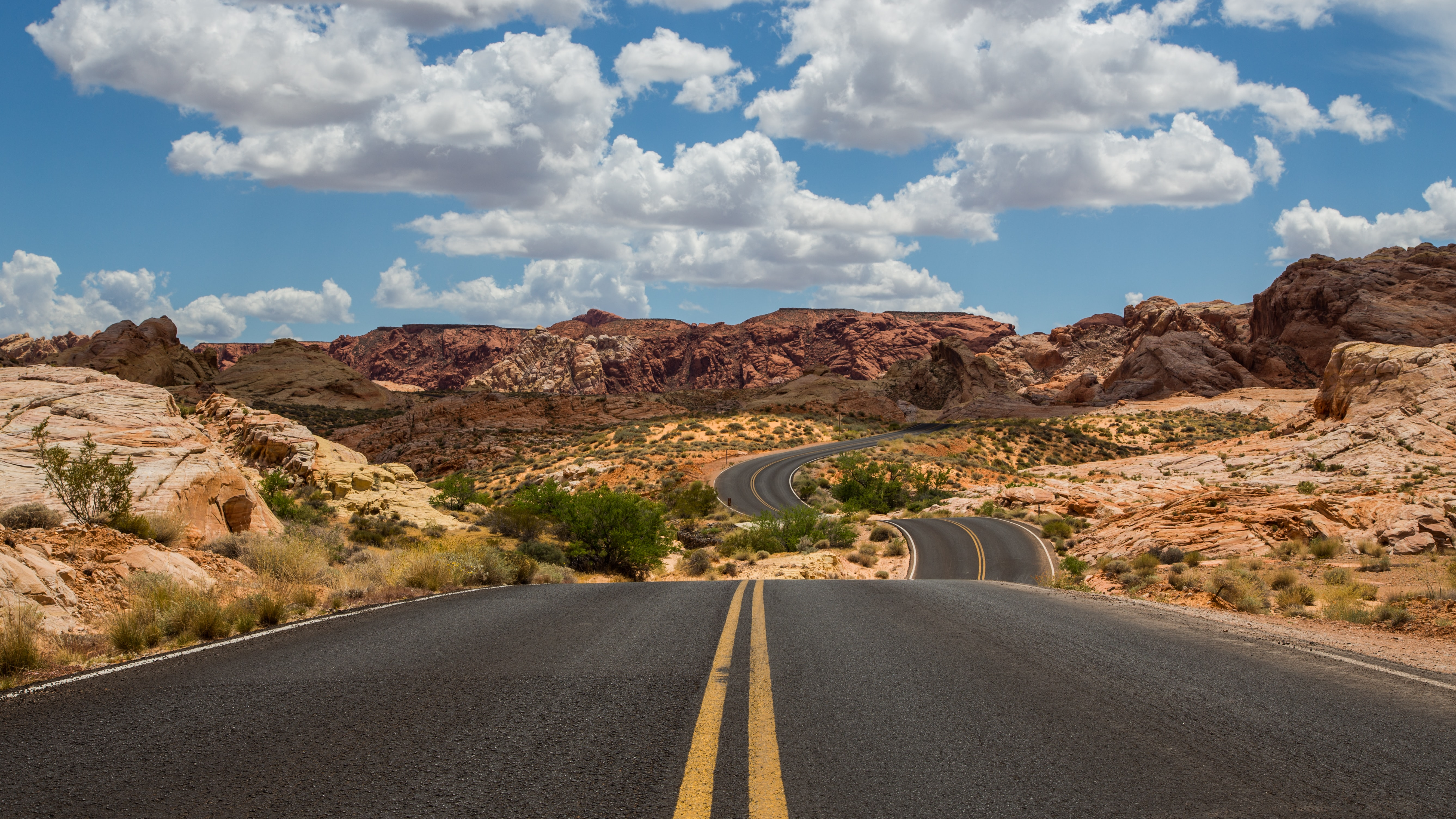 Image of an open road with mountains in the background.